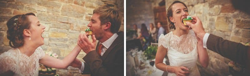 The bride and groom push cakes into each others mouths