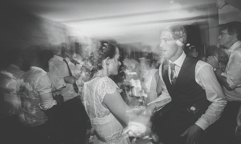 The bride and groom on the dancefloor dancing with friends and family