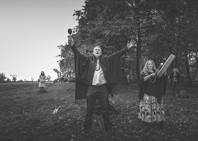 The wedding celebrant holds his arms up in the air during the pagan ceremony