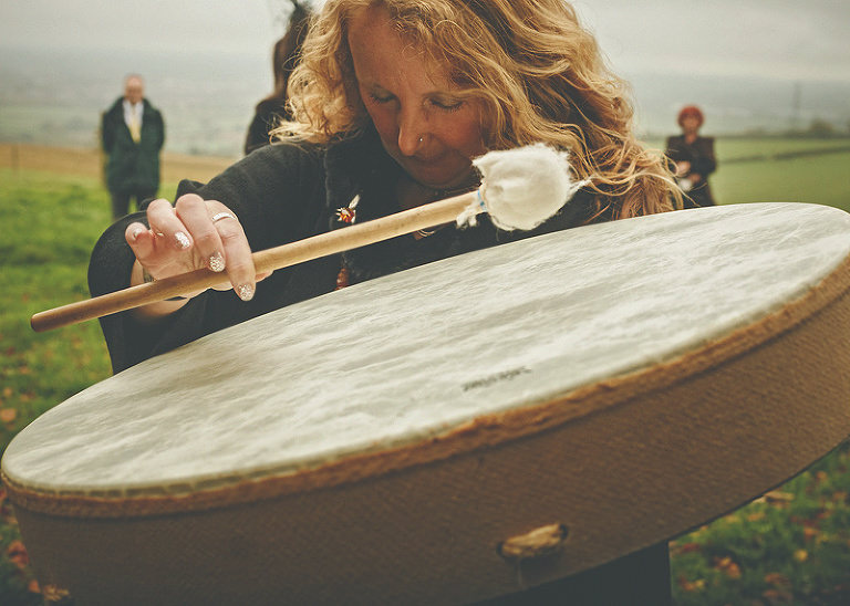 A lady places her head next to the drum bangs on it during the pagan ceremony