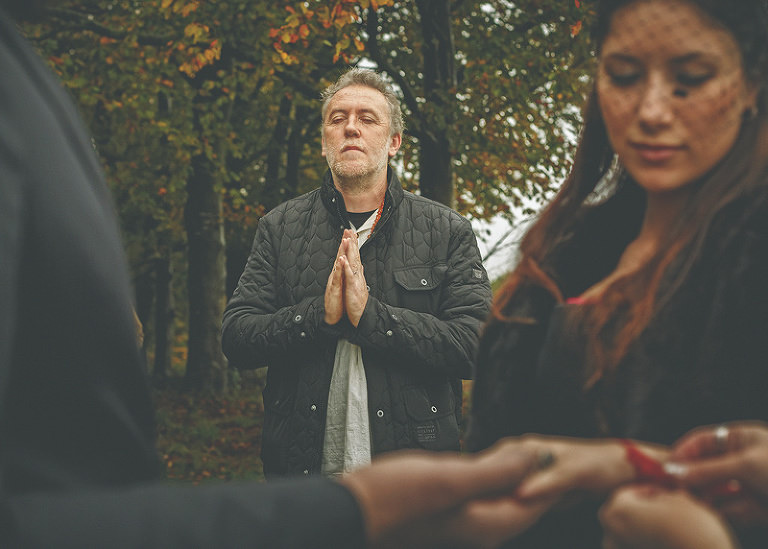 A man holds his hands together and prays during the pagan ceremony