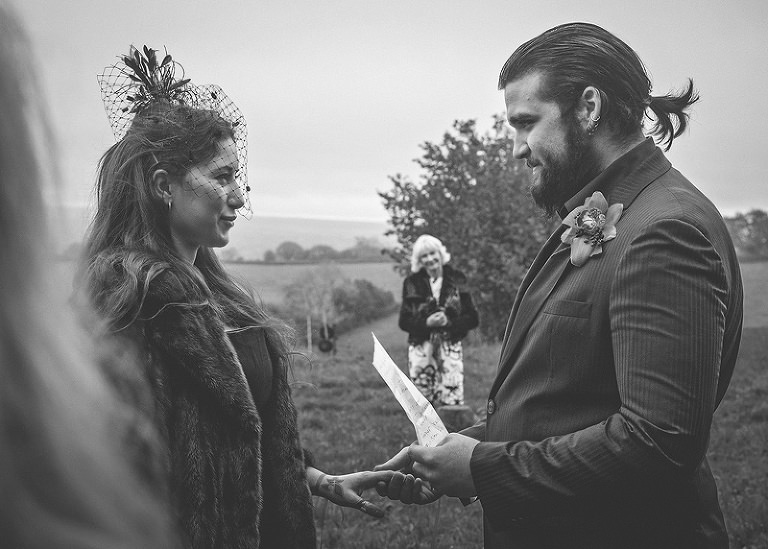 The groom stands in front of the bride and reads a poem to her