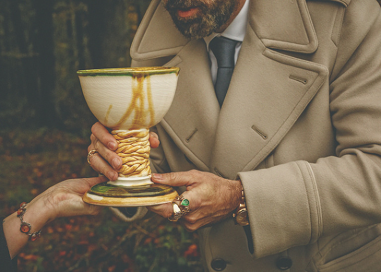 A wedding guest holds a large goblet in his hand