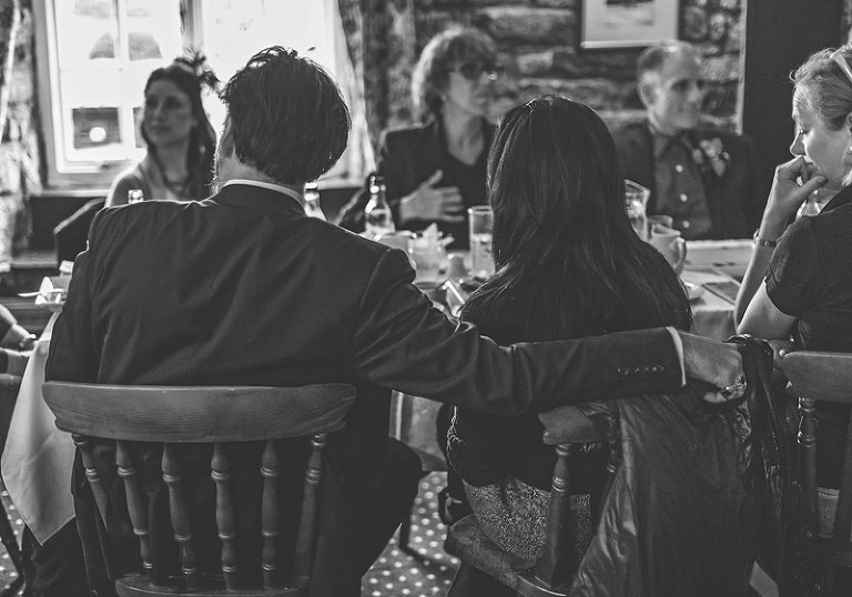 A wedding guest places his arm around his wifes shoulder sat at the wedding ginner table