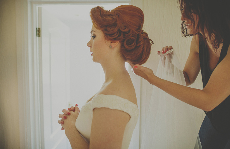The make up artist puts on the brides veil
