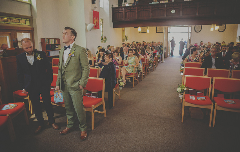 The groom and the best man stand nervously as they wait for the bride to enter the church