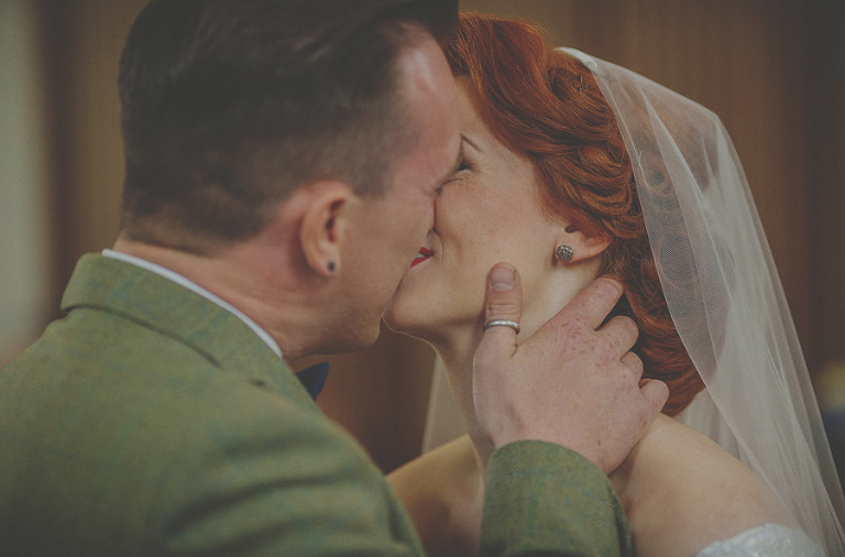 The bride and groom kiss each other during the wedding ceremony