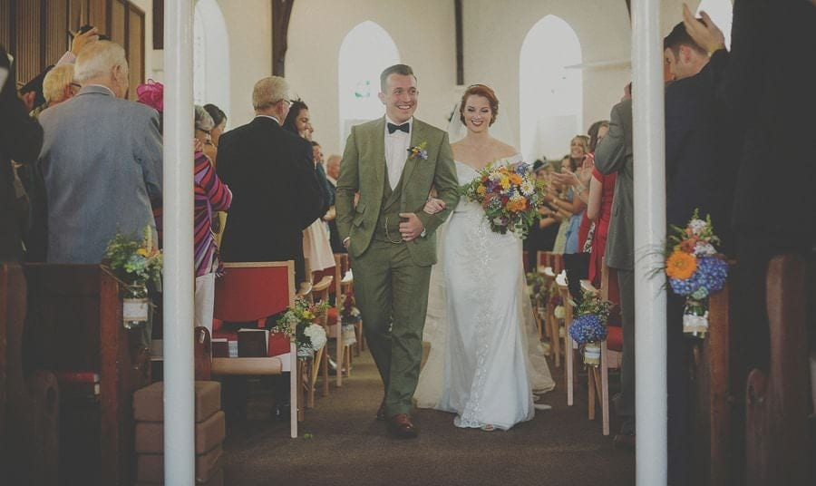 The bride and groom walk up the aisle together in church