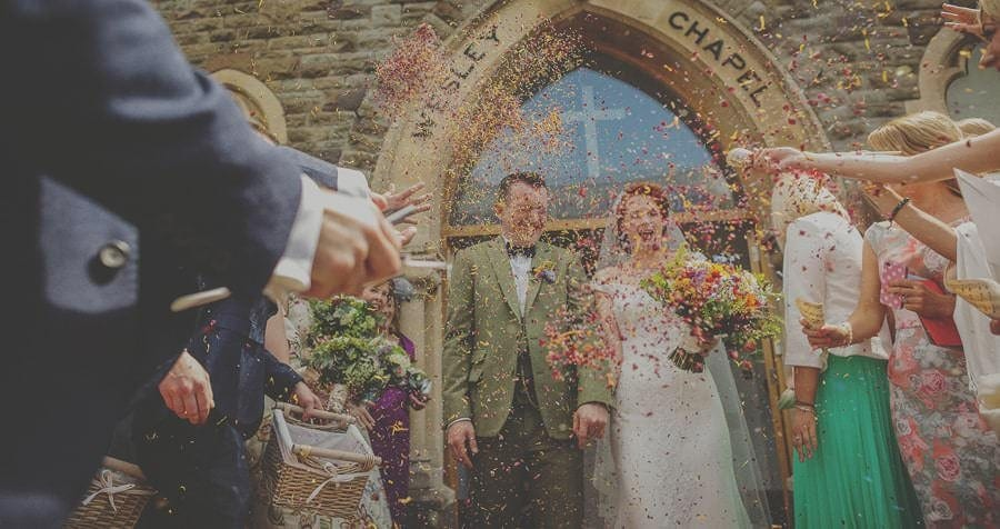 The bride and groom are showered with confetti