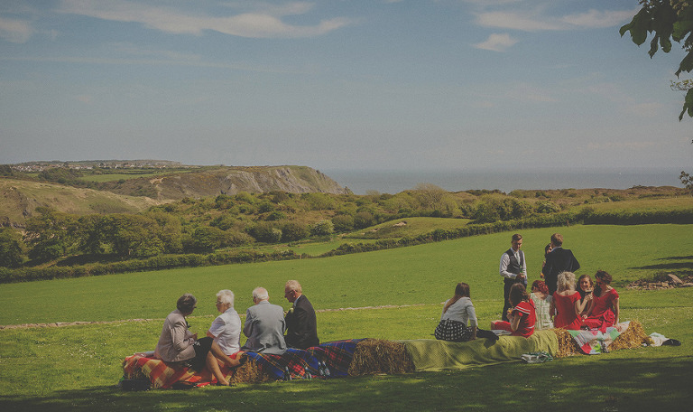 Wedding guests sit on hay bails in the garden of Penmaen house