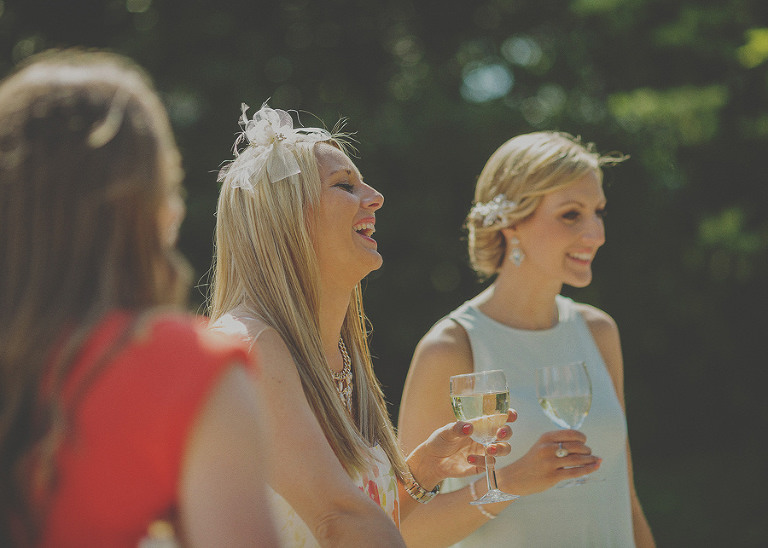 A lady holding a champagne glass laughs with friends