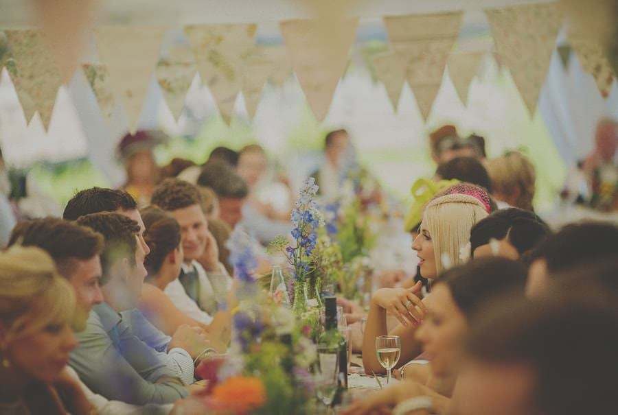 Wedding guests talk as they sit in the marquee