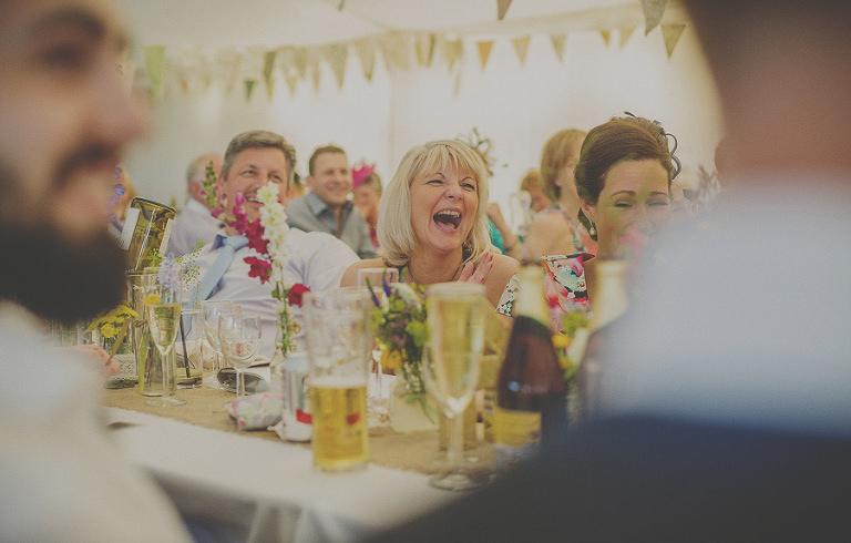 A wedding guest laughs in the marquee at Penmaen house