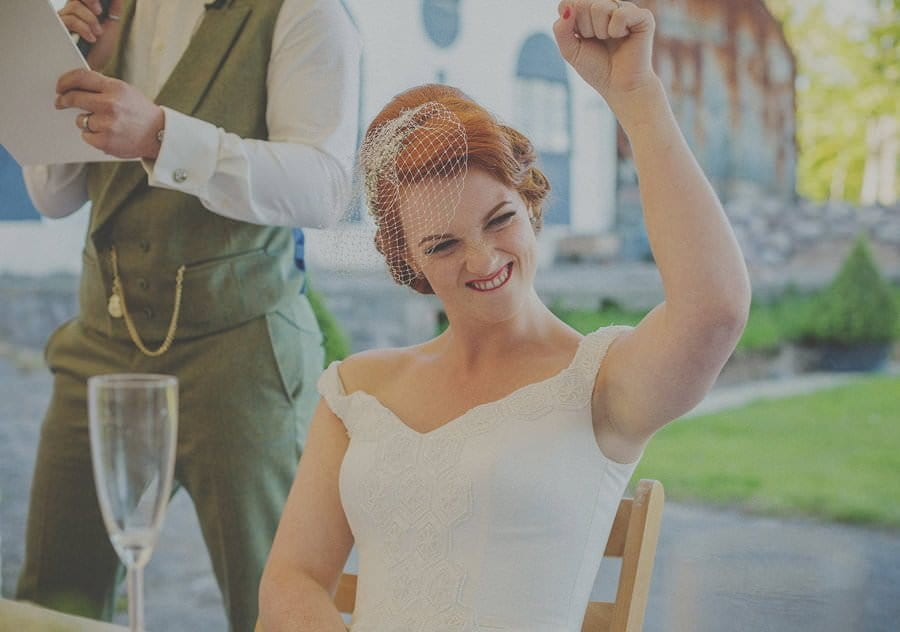 The bride raises her arm and smiles