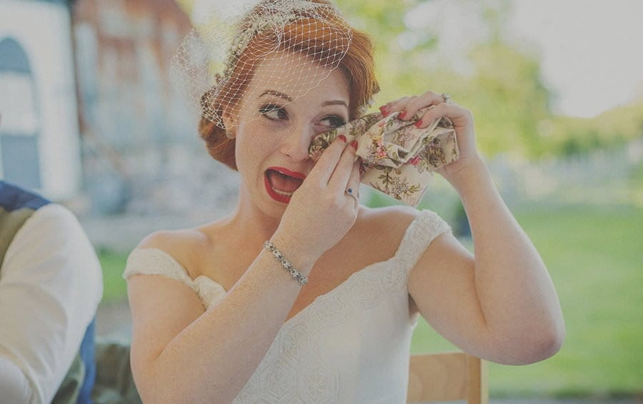 The bride wipes a tear from her eye