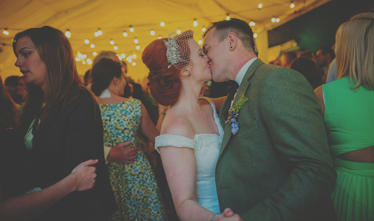 The bride and groom kiss each other on the dancefloor