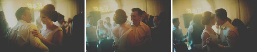 The bride and groom hold each others hand and dance together