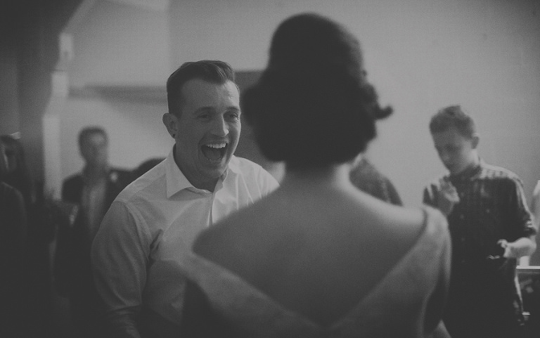The groom laughs at his bride on the dancefloor