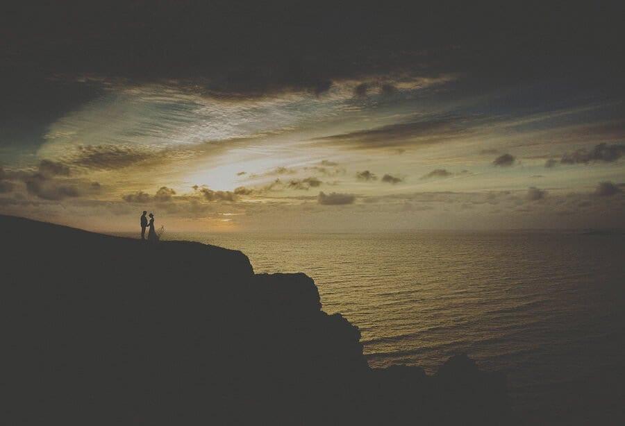 The bride and groom watch the sun go down at Rhosilli beach