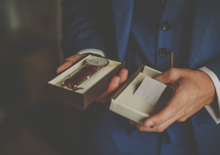The groom opens his gift of a watch from the bride