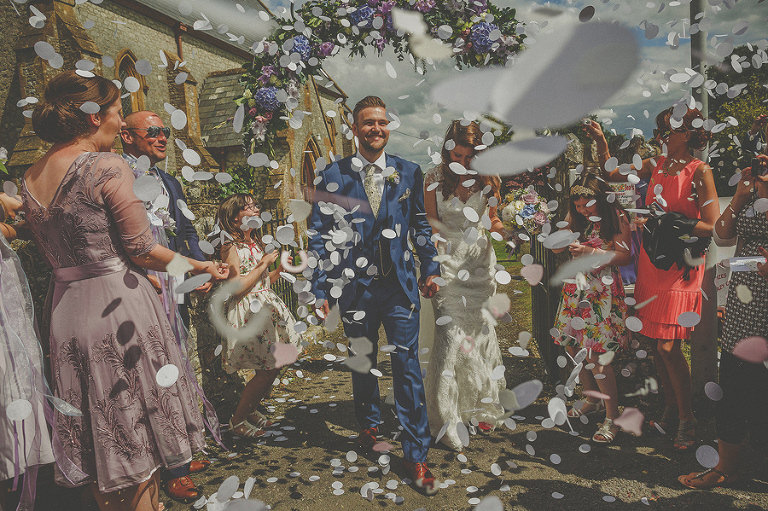 Guests throw confetti as the bride and groom leave the church