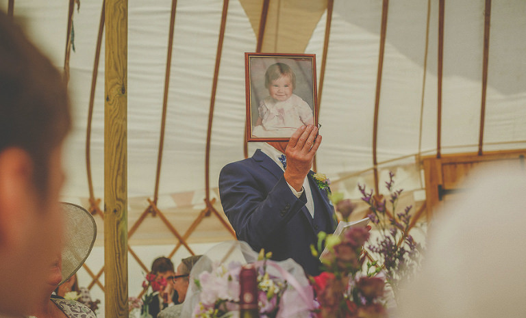 The brides father holds up a photograph of the bride