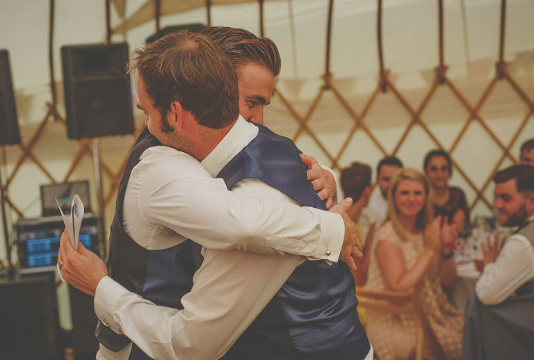 The groom hugs the best man