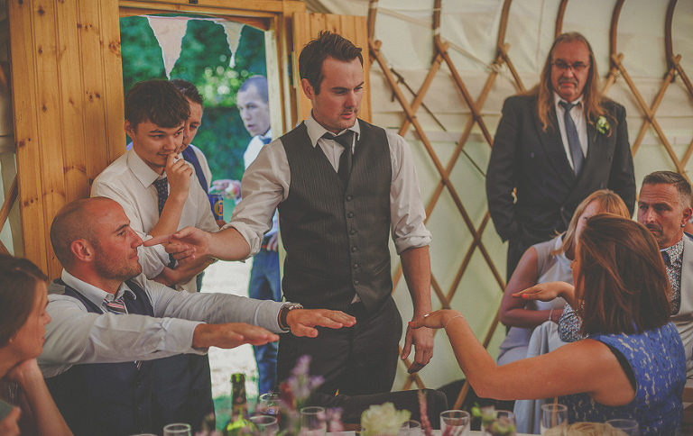 The wedding magician performs a trick for the guests