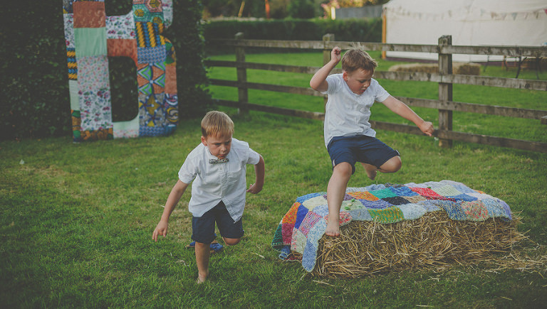 Two boys jump over haystacks