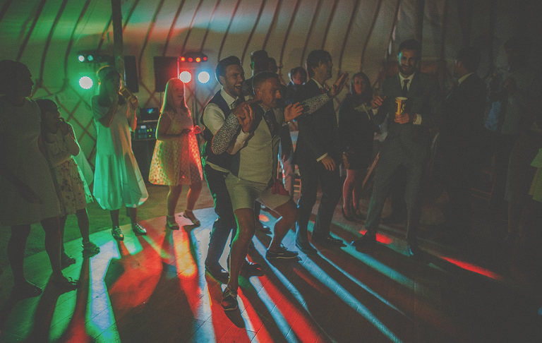 The groom dances with a friend on the dancefloor