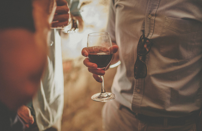 A glass of wine held by a guest