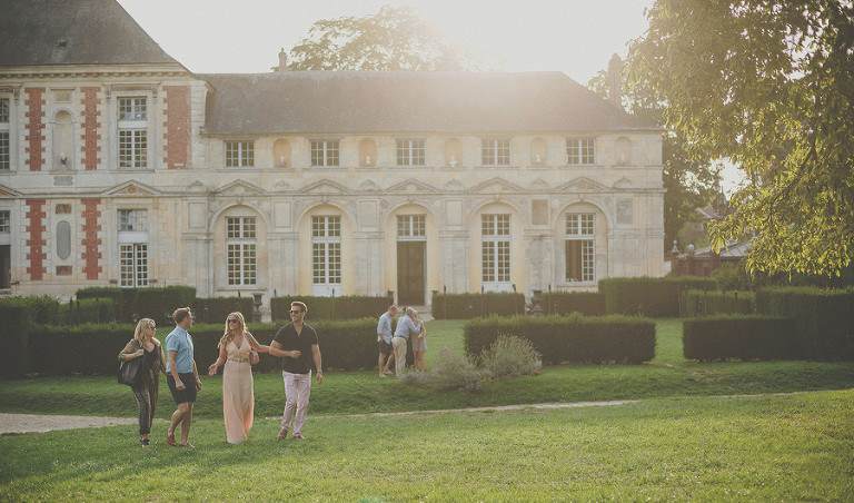 Wedding guests walk away from the wine cellar as the sun goes down