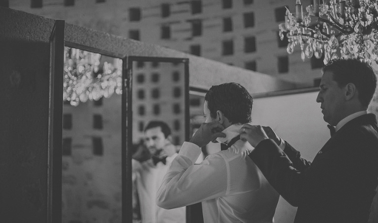 The groom puts on his tie