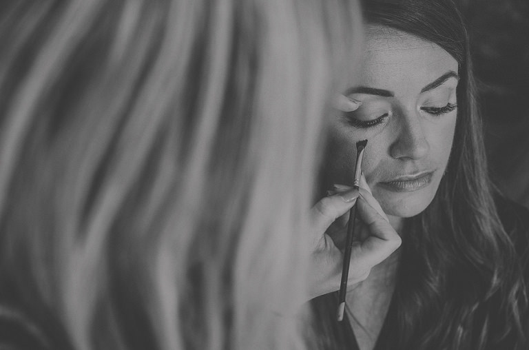 The make up artist applies make up onto the brides face