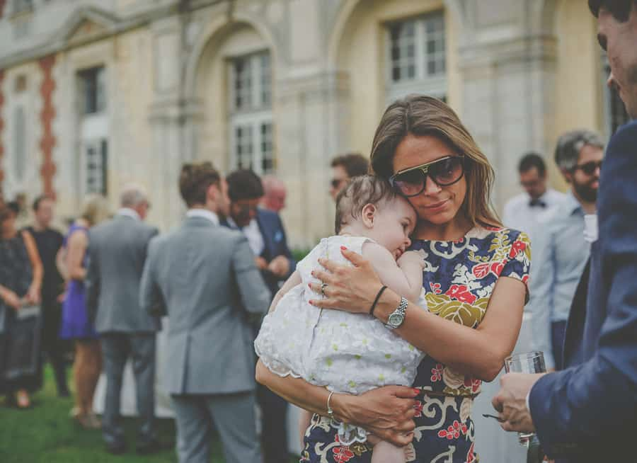 A wedding guest holds her daughter on the front lawn
