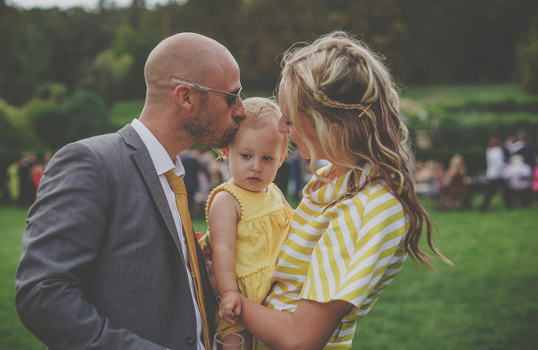 A father kisses his daughter on the head