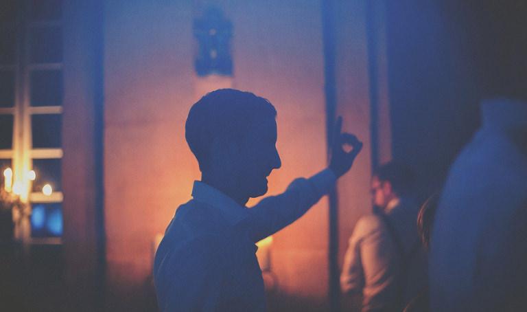 A wedding guest raises an arm as he dances