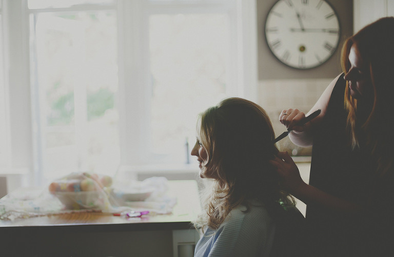 The hairdresser combs the back of the brides hair