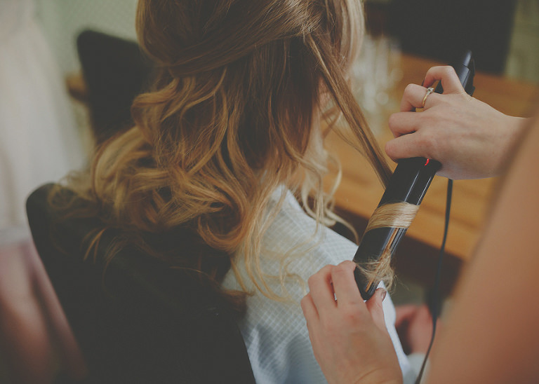 The hairdresser curls the brides hair
