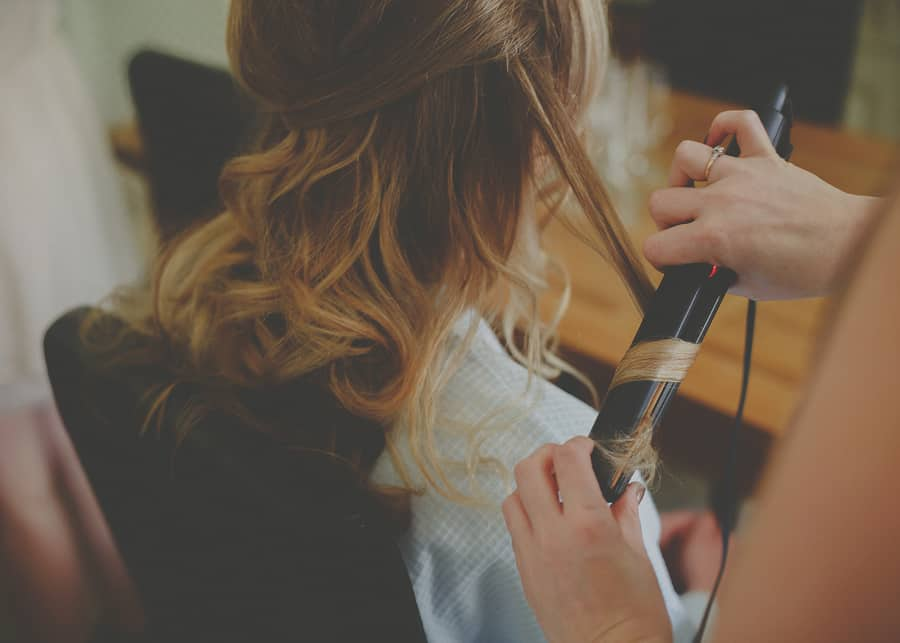 The hairdresser curls the brides hair