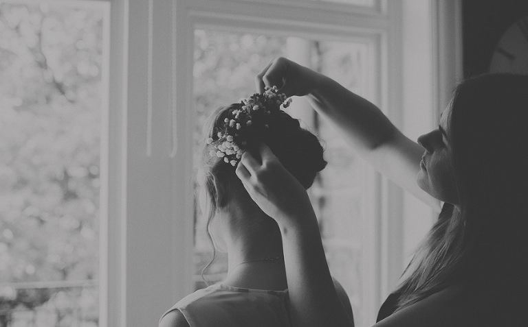 A hairdresser places flowers onto the back of a bridesmaids head