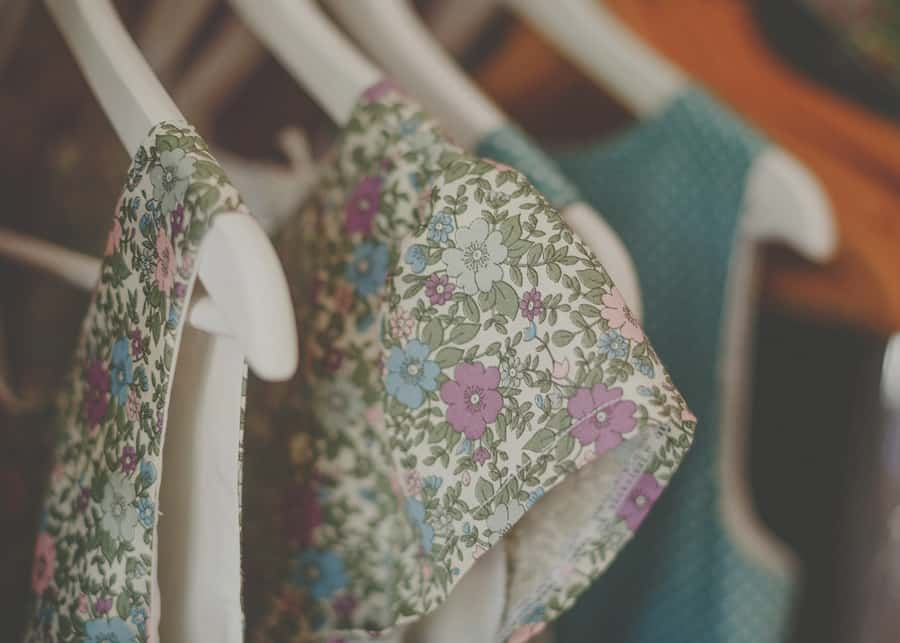 The bridesmaids dresses hang in the cupboard