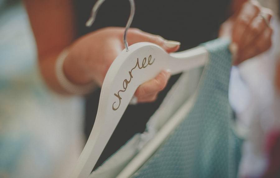 A bridesmaid picks up her dress