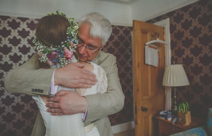 The brides father embraces his daughter and smiles