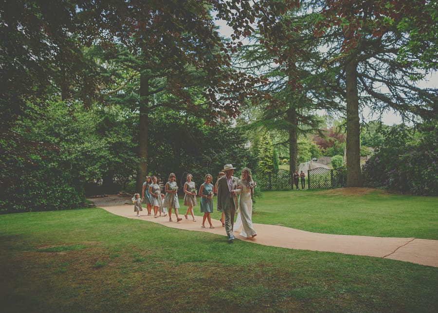 The wedding party walk across the lawn at Markington Hall