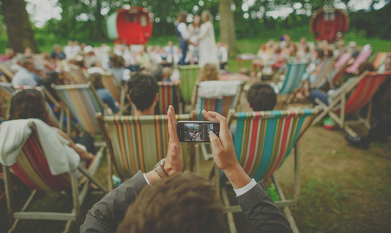 A wedding guest takes a photograph of the wedding ceremony on his mobile phone
