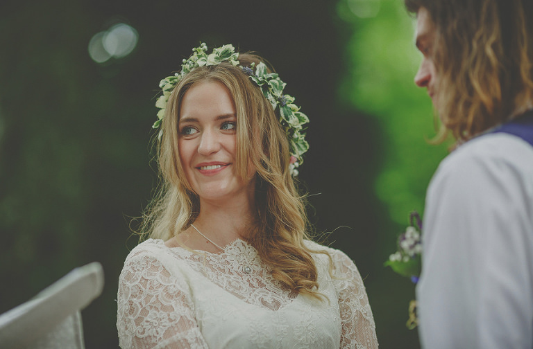 The bride looks away and smiles at a wedding guest