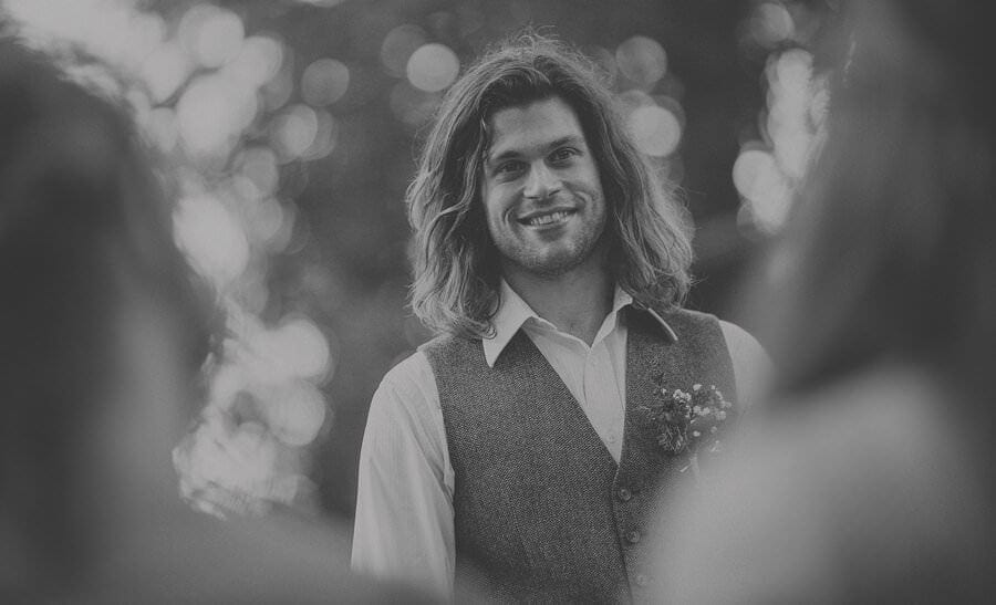 The groom smiles at the bride during the outdoor wedding ceremony