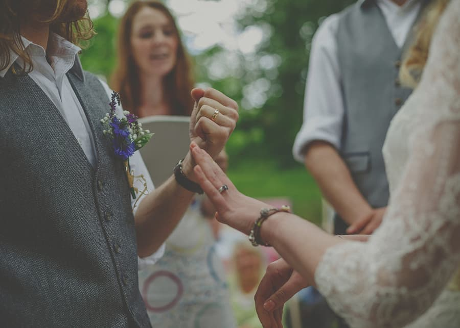 The bride and groom show their rings to each other during the wedding ceremony