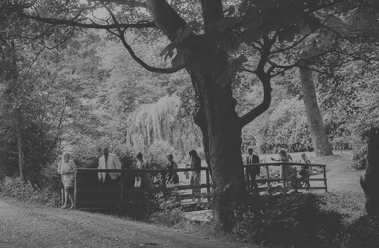 Wedding guests walk across the wooden bridge at Markington Hall